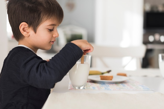 Front view kid dipping biscuit in milk Free Photo