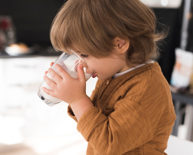 Front view kid drinking glass of milk Free Photo