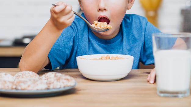 Front view kid eating cereal Free Photo