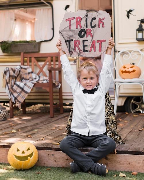 Вид спереди ребенок держит знак трюк или угощение Бесплатные Фотографии