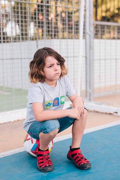 Front view of kid sitting on ball Free Photo