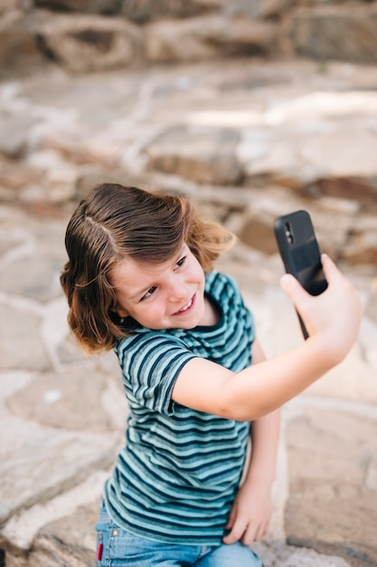 Front view of kid taking a selfie Free Photo