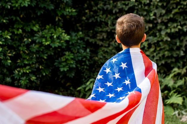 Вид спереди ребенок, носящий флаг сша Бесплатные Фотографии