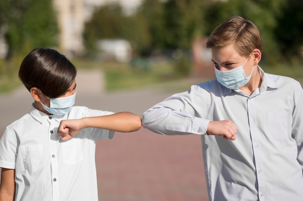 Front view of kids greeting with elbow bump Free Photo