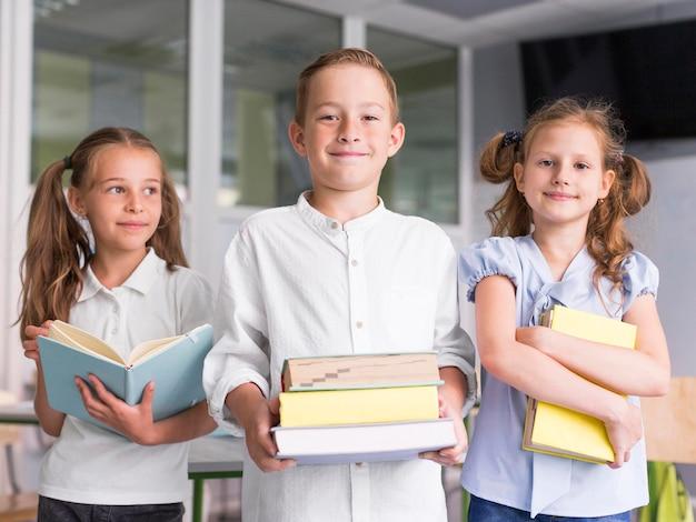 Вид спереди дети, держащие книги в классе Premium Фотографии