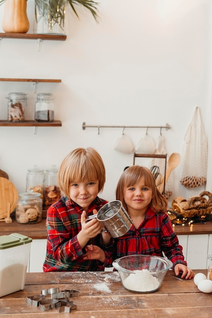 Bambini di vista frontale che producono i biscotti di natale Foto Gratuite