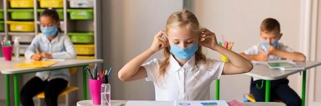 Bambini di vista frontale che si proteggono con maschere mediche Foto Gratuite