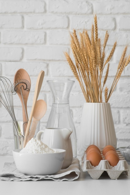 Front view kitchen tools arrangement and eggs Free Photo