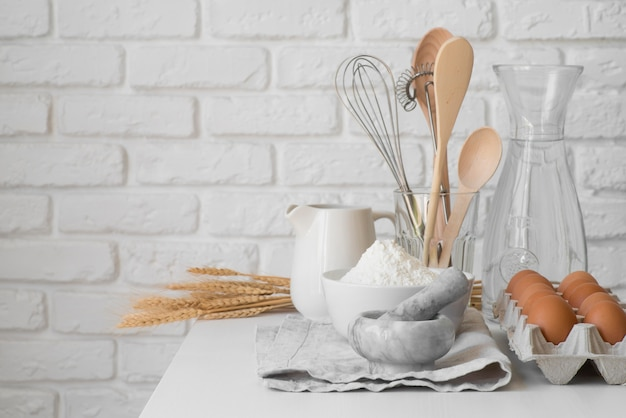 Front view kitchen utensils arrangement and eggs Free Photo