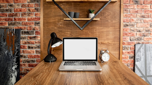 Front view of laptop on office workspace with lamp Free Photo