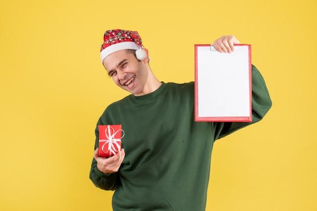 Вид спереди смеющегося человека с зеленым свитером, держащего буфер обмена и подарком, стоящего на желтом Бесплатные Фотографии