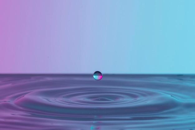 Vista frontale della spruzzata di liquido dalla goccia trasparente Foto Gratuite