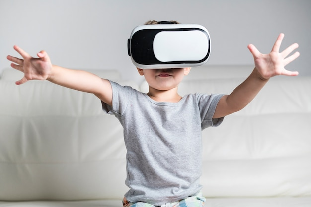 Front view little boy enjoying a pair of vr headset Free Photo