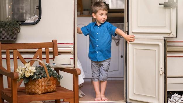 Маленький мальчик, открывающий дверь каравана, вид спереди Бесплатные Фотографии