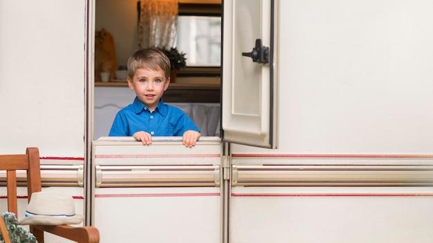 Вид спереди маленький мальчик, стоящий перед дверью каравана Бесплатные Фотографии