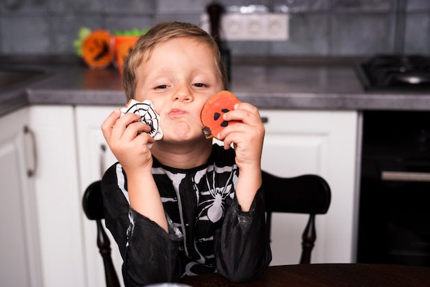 Front view of a little boy with cookies Free Photo