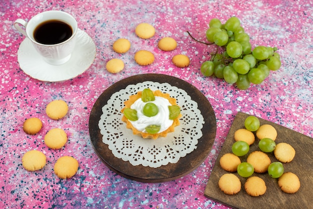Front view little cake with cream cup of tea cookies and along with green grapes on the bright surface cake fruit Free Photo