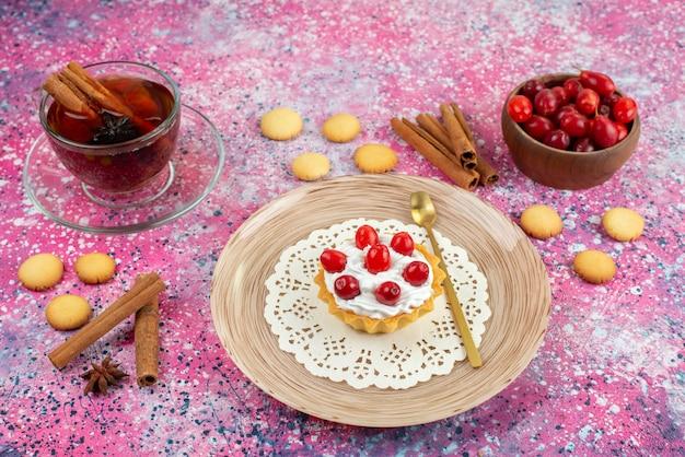 明るいデスクケーキ甘い上にシナモンと紅茶のカップと共に新鮮なクリームと新鮮な果物の小さなケーキの正面図 無料写真