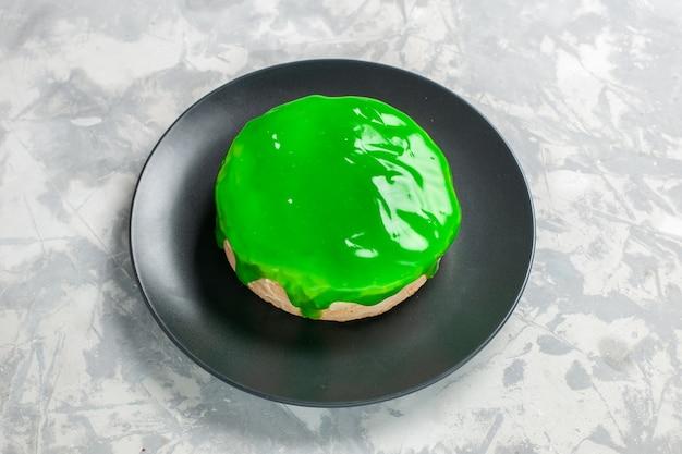 Маленький торт с зеленой глазурью на белом столе, вид спереди Бесплатные Фотографии