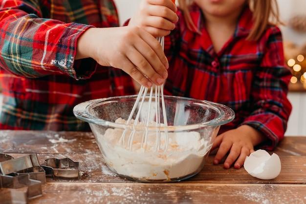 Vista frontale piccoli bambini che producono i biscotti di natale Foto Gratuite