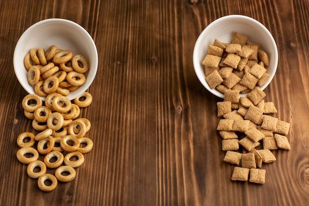 茶色の木製の机の上の小さなクッキーとクラッカーの正面図 無料写真