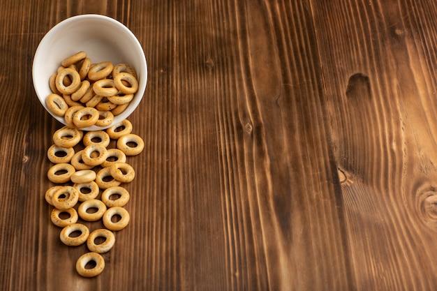 Вид спереди маленькие крекеры внутри тарелки на деревянной поверхности Бесплатные Фотографии