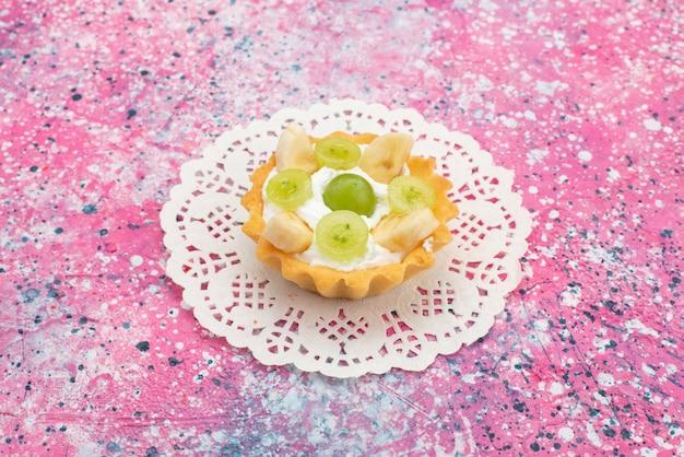 正面の色の表面に甘いクリームとスライスされたフルーツの小さなおいしいケーキ 無料写真
