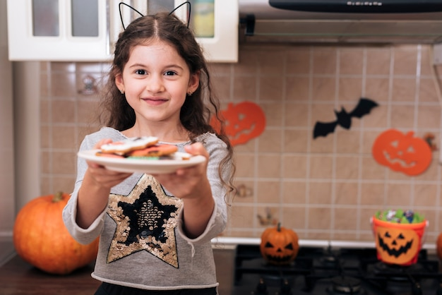 Front view of a little girl with a plate of cookies Free Photo