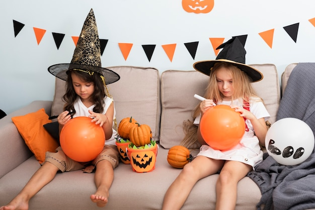 Front view little girls sitting on couch on halloween Free Photo