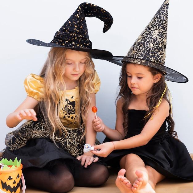Вид спереди маленьких девочек, сидя на полу на хэллоуин Бесплатные Фотографии