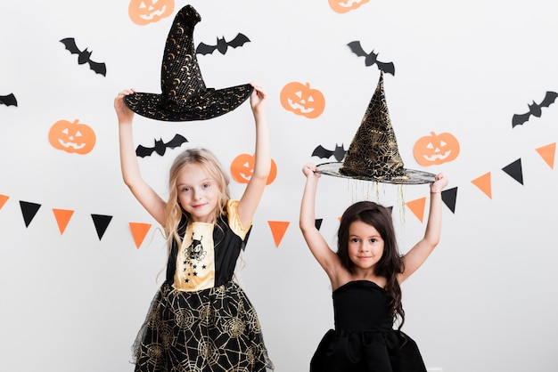 Front view little girls in witch costume for halloween Free Photo