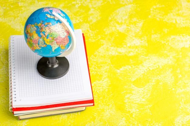 Вид спереди маленький глобус с тетрадями на желтой поверхности Бесплатные Фотографии