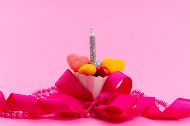 Un piccolo regalo di vista frontale con caramelle e candela d'argento progettata con rosa, fiocco isolato su rosa, presente festa di compleanno Foto Gratuite