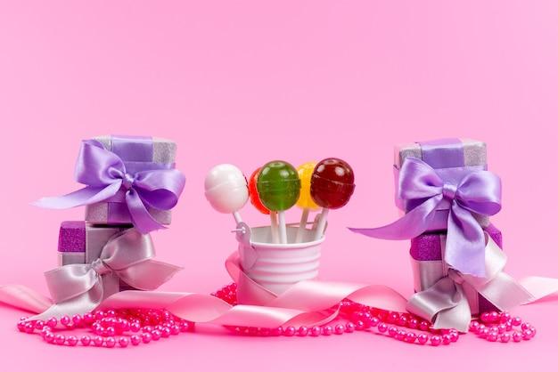 Una vista frontale lecca-lecca e scatole regalo viola isolati su rosa, festa di compleanno Foto Gratuite