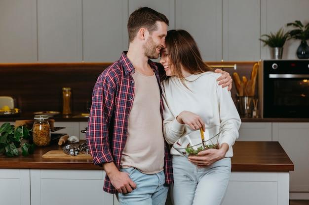 Vista frontale delle coppie amorose che preparano il cibo a casa Foto Gratuite