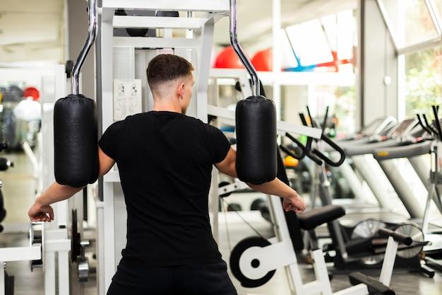 Мужчина вид спереди в тренажерном зале, делая упражнения Бесплатные Фотографии
