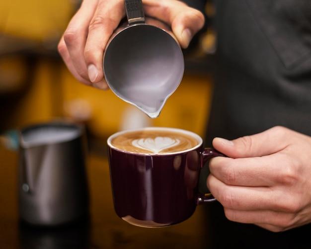Vista frontale del barista maschio versando il caffè in tazza Foto Gratuite