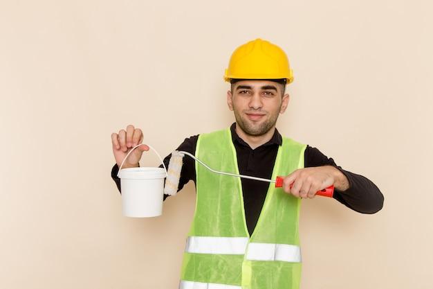 黄色いヘルメットペイントを押しながらライトデスクでポーズの正面の男性ビルダー 無料写真