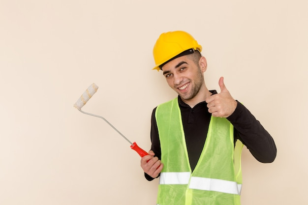 Front view male builder in yellow helmet holding brush for walls smiling on light background Free Photo