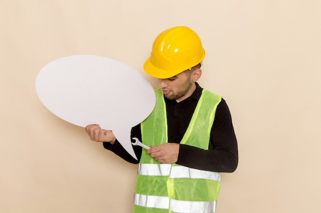 Front view male builder in yellow helmet holding white sign and tool on the light background Free Photo