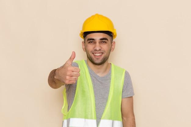 Generatore maschio vista frontale in casco giallo sorridente e in posa su sfondo crema Foto Gratuite