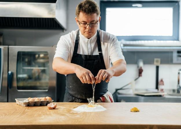 Vista frontale del cuoco unico maschio che rompe l'uovo sopra la farina per creare la pasta Foto Gratuite