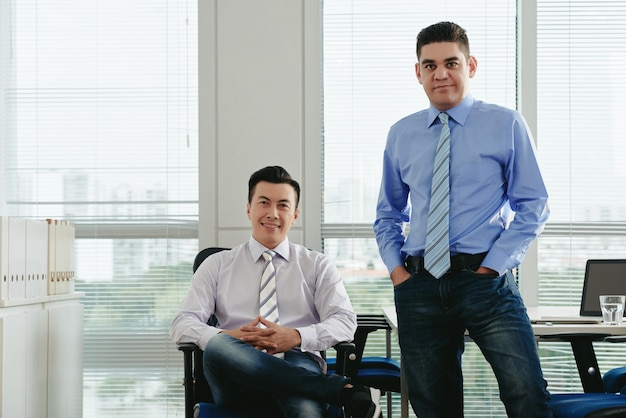 Front view of male colleagues looking at camera in their office Free Photo