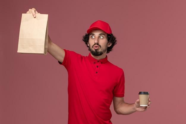 明るいピンクの壁サービス配達従業員労働者に茶色のコーヒーカップと食品パッケージを保持している赤いシャツとケープの正面図男性宅配便配達人 無料写真