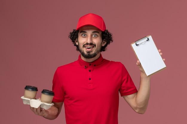 밝은 분홍색 벽 서비스 배달 직원 작업 작업에 갈색 배달 커피 컵과 메모장을 들고 빨간 셔츠와 케이프에 전면보기 남성 택배 배달 남자 무료 사진