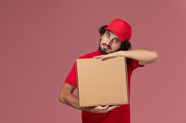 Вид спереди мужчина курьерской доставки мужчина в красной рубашке и накидке держит коробку с доставкой еды на розовом столе сотрудника службы доставки Бесплатные Фотографии