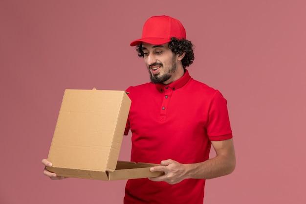 Вид спереди мужчина курьерской службы доставки в красной рубашке и накидке держит коробку с едой на розовой стене сотрудника службы доставки Бесплатные Фотографии