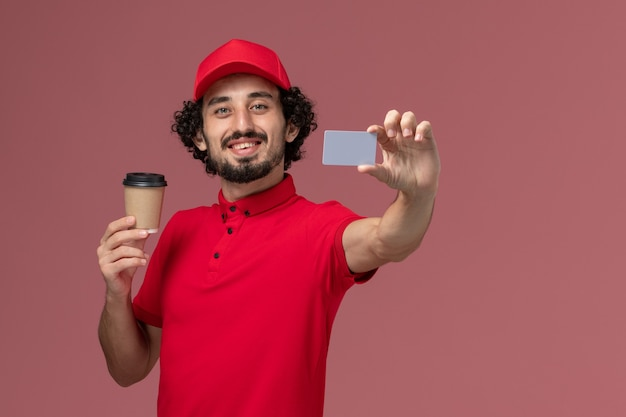 Front view male courier delivery man in red shirt and cape holding brown coffee cup with grey card on light-pink wall service uniform delivery employee male Free Photo