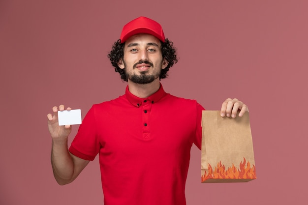 Front view male courier delivery man in red shirt and cape holding food package and card on the pink wall service delivery employee Free Photo