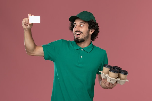 Front view male courier in green uniform and cape holding coffee cups with card on the pink background service uniform delivery job Free Photo